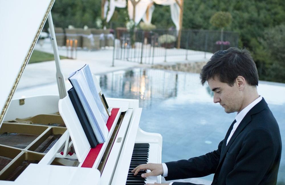 pianista con piano de cola blanco